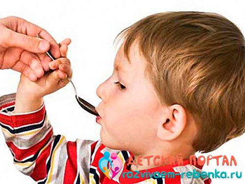 Мальчик пьет активированный уголь из ложки