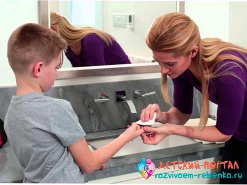Мама обрабатывает руку сына после удаления занозы
