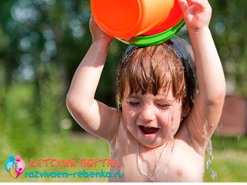 Ребенок закаляется, обливаясь водой из ведра