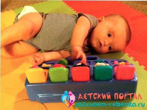 Ребенок перевернулся на бок и пытается дотянуться до игрушки фото