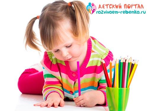 Маленький ребенок пишет буквы зеркально левой рукой