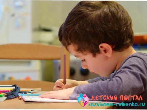 Мальчик учится писать буквы