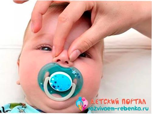 Мама держит носик новорожденного рукой
