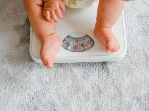 Взвешивание маленького ребенка Фото