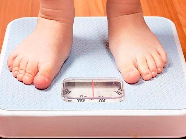 Взвешивание ребенка при помощи напольных весов Фото