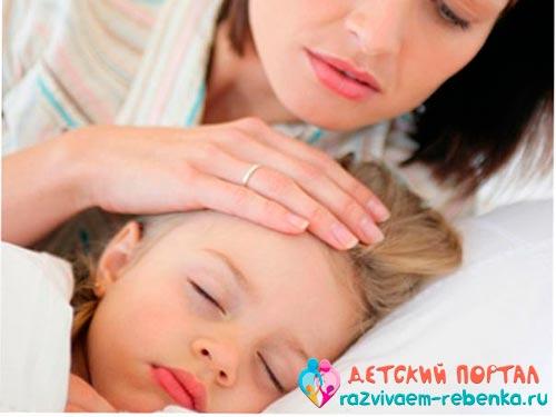 Мама пробует лоб у ребенка на наличие температуры