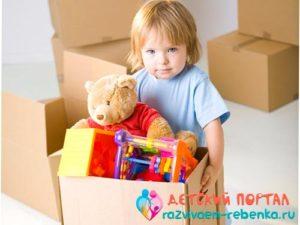 Ребенок несет коробок с игрушками на свое место