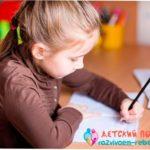 Девочка левша пишет буквы в зеркальном отражении