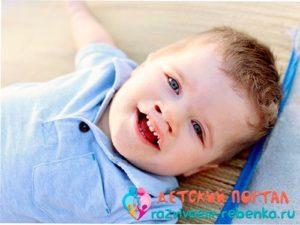 Мальчик двух лет лежит на спине